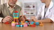 canvas print picture - Hospital worker helping dementia patient combine color blocks, brain exercise