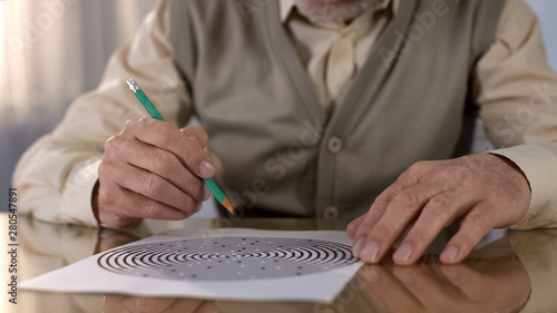 Concentrated retired man solving logic test at table, memory exercise, neurology Fototapeta