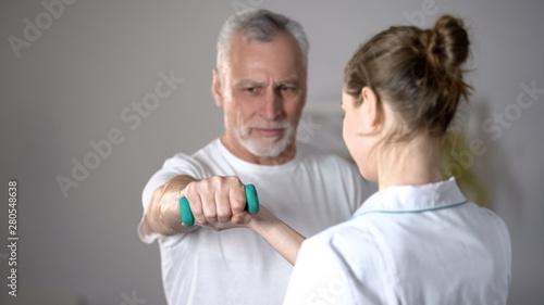 Fotografia Nurse helping old man to lift dumbbell, cardiac rehabilitation, injury recovery
