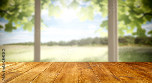 Table background and spring time. Green garden outside the winfow in blurred view. Empty space for decoration and an advertising product.