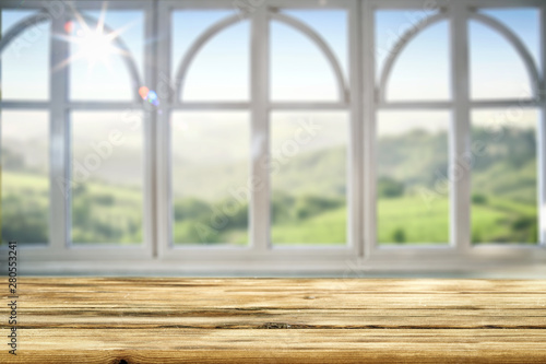 Table background and spring time. Green garden in blurred view outside the window. Empty space for decoration and an advertising product.
