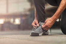 A Single Man Tying His Shoelaces, Ready To Start Exercising For An Upcoming Marathon