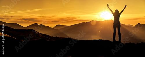 Fotografie, Obraz Frau in Siegerpose bei Sonnenaufgang auf einem Berggipfel