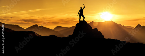 Foto Frau in Siegerpose bei Sonnenaufgang auf einem Berggipfel