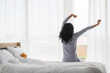 Asian woman stretch lazily in bedroom..