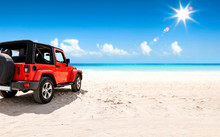 A Red Jeep On Sandy Beach And Beuatiful Blue Sunny Sky View In Summer Time.