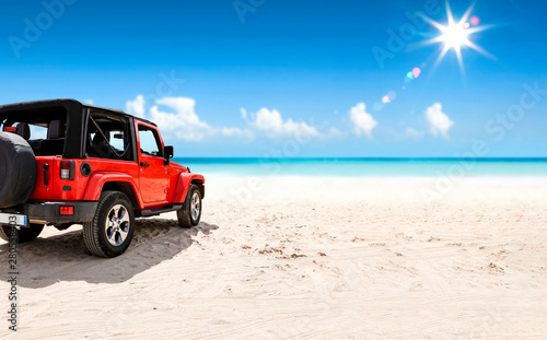 mata magnetyczna A red jeep on sandy beach and beuatiful blue sunny sky view in summer time.