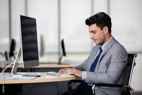 Fototapety, obrazy: Businessman sitting and using computer..