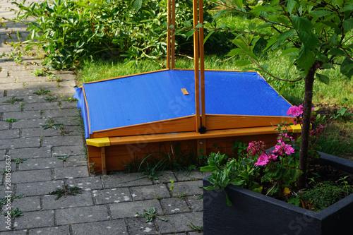 Fotografie, Obraz a sandbox with sandbox cover in the garden on a warm day