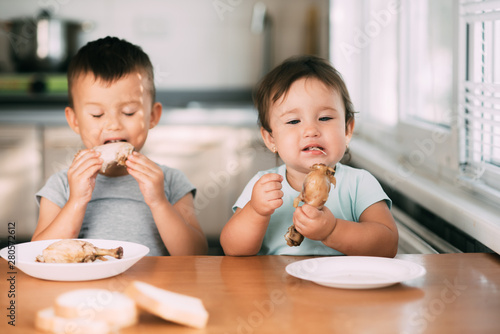 Fototapeta Kids boy and girl , brother and sister in the kitchen having fun and eating chicken with appetite obraz na płótnie