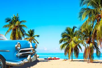 Tropikalna plaża Varadero na Kubie z amerykańskim klasycznym samochodem, żaglówkami i palmami w letni dzień z turkusową wodą. Tło wakacje.