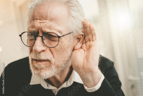 Foto  Senior man with hearing problems