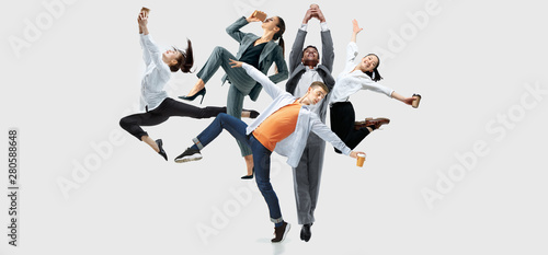 Fotografia  Happy office workers jumping and dancing in casual clothes or suit with folders on white