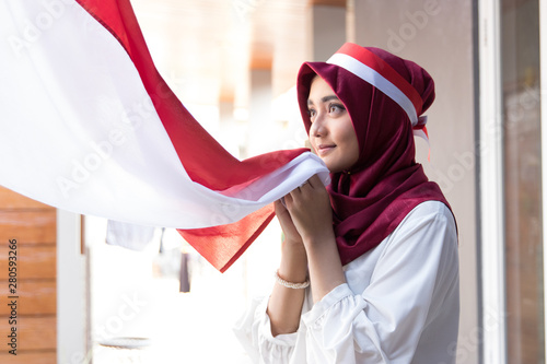 Fotomural  portrait of young asian woman with scarf kissing red and white flag of indonesia