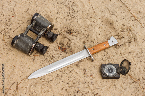 Fotografie, Obraz Knife bayonet with wooden handle lies on the sand with old military binoculars and old compass