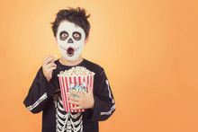 Happy Halloween.Surprised Child In A Skeleton Costume With Popcorn