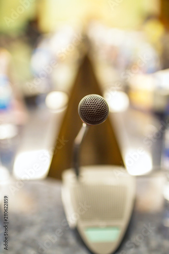 Microphone on table in meeting room with blurred business conference; selective focus.