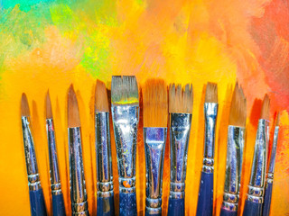 Acrylic paint brushes with colourful background