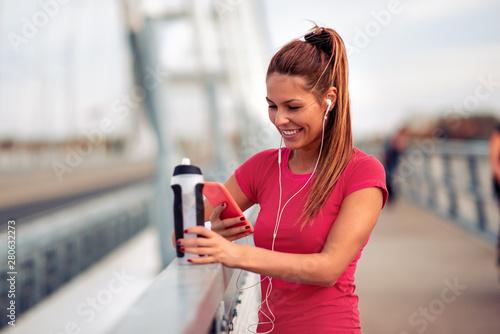 plakat Happy female runner jogging over the bridge