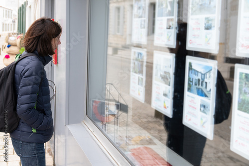 Fotomural  woman in front of the window of a real estate agency