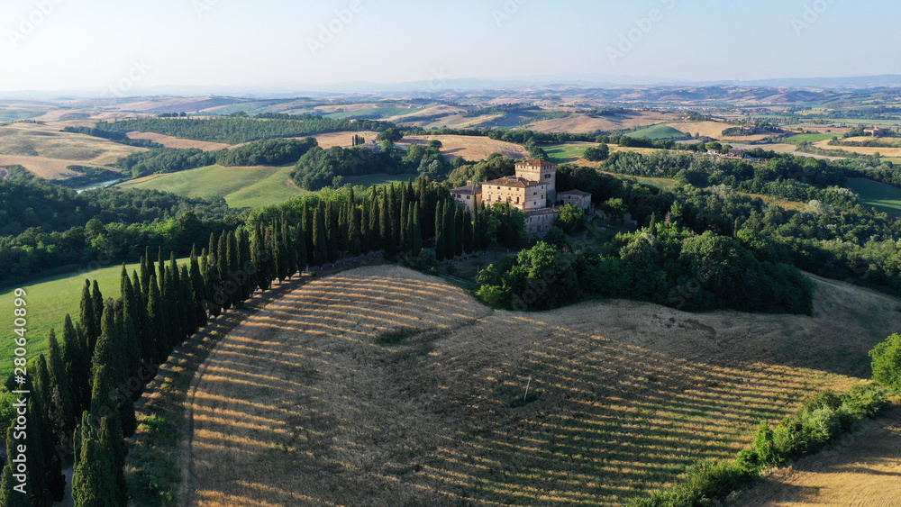 Aerial view of a Buonconvento castle villa with cypress trees road, hills at sunset. Val d'Orcia, Tuscany, Italy