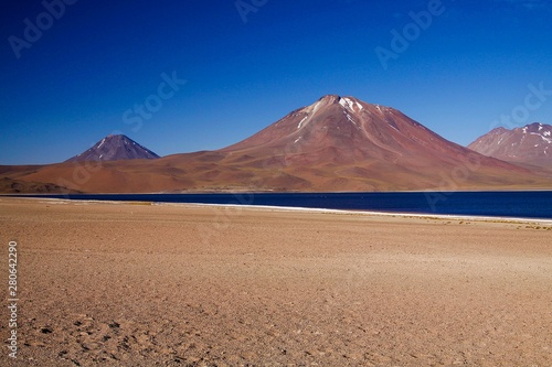 Cadres-photo bureau Desert de sable View on deep blue lake at Altiplanic Laguna (Lagoon) Miscanti in Atacama desert with partly snow capped cone of volcano Meniques in the background - Chile