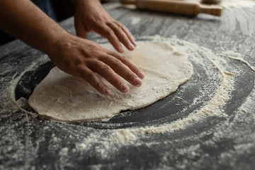 The chef in the kitchen rolls out the pizza dough. Male baker hands