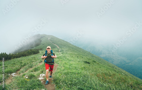 Fotografie, Obraz  Happy hiker man walking by the cloudy and foggy weather mountain range path with backpack