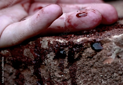 Fotomural Human hand lies limp on the ground in a pool of blood