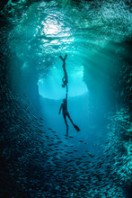 Free Diving Couple In Love Holding Each Others Hand Underwater In The Cavern With Back Light