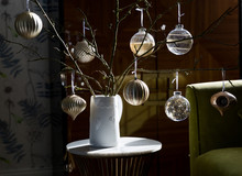 Gold Toned Christmas Baubles Displayed On A Sunny Table. Alternative Christmas Tree.