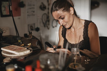 Female Jeweler Sitting At Her Workbench Using An Engraving Tool