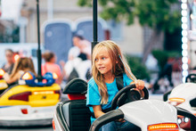 Little Girl In Cars Bumper In Fair.