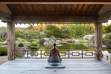 Woman Meditating In Japanese Meditation Garden