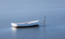 A Small White Rowboat Blurred Against Blue Water