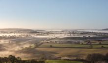 Looking Across Misty Fields To The Sea.
