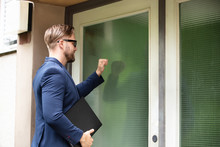 Man Standing In Front Of The House Knocking The Door