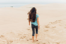 Girl Walking On Sand On A Windy Day