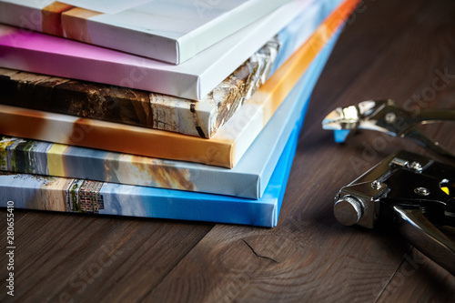Fototapeta Photography canvas prints. Stack of colorful photos with gallery wrapping method on wooden table. Stretching tools: staple gun and canvas pliers obraz