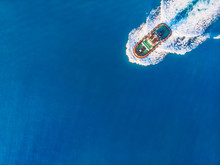Tugboat Sails To Meet Liner Or Cargo Ship In Port. Top View Of Blue Ocean