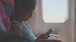 Adorable girl traveling by an airplane and using a digital tablet during the flight. Concept traveling abroad with kids.