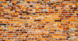 Leinwanddruck Bild - Old and weathered grungy yellow and red brick wall as seamless pattern texture surface background in wide banner format.