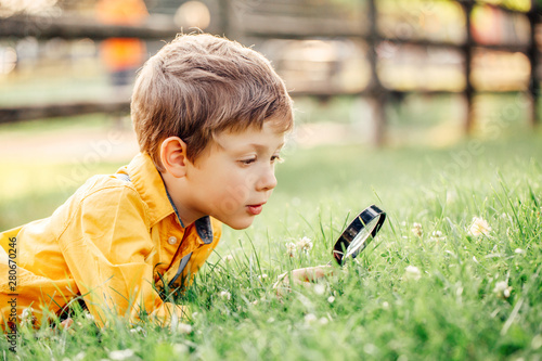 Valokuva Cute adorable Caucasian boy looking at plants grass in park through magnifying glass