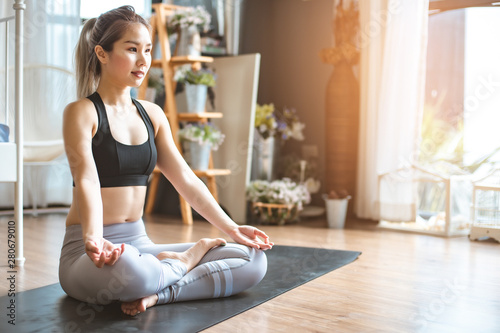 Fotomural  Young woman practicing yoga in  gray background
