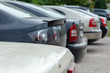 Row of cars and vans parked in parking lot during the daytime. The back of the trunk is visible in the parking space on blurred background. Transportation and parking.