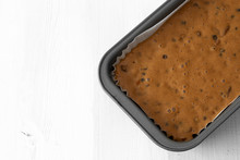 Fruit Cake Loaf Mixture In A Metal Baking Tin.  On A White Wood Background