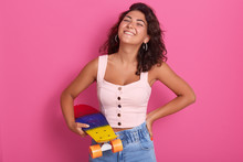 Magnificent Girl With Charming Smile In Casual Fashionable Clothes Posing With Skateboard In Hands. Studio Portrait Of Beautiful Female Posing Isolated Over Pink Background. People Emotion Concept.