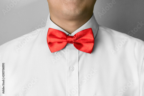 Fotografering Man ties a red bowtie at the collar
