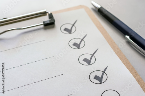 Fotografía Abhaken einer Checkliste auf einem Klemmbrett