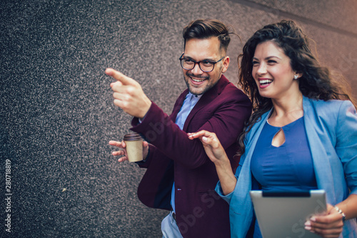 Fototapeta  Handsome man and beautiful woman as business partners using digital tablet outdo